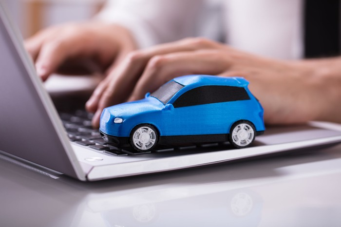 A model of a blue car sits on top of a laptop.