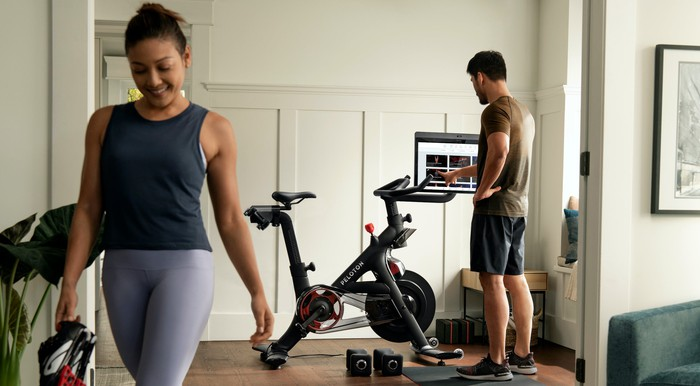 Woman wearing workout clothes walking away from Peloton Bike while man standing next to it reaches towards the screen