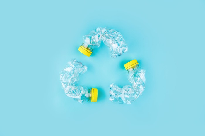 crushed plastic water bottles arranged to form the recycling symbol.
