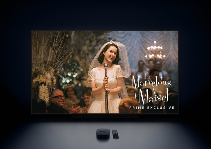 """Apple TV set-top box next to remote in front of TV showing a still from """"The Marvelous Mrs. Maisel"""""""