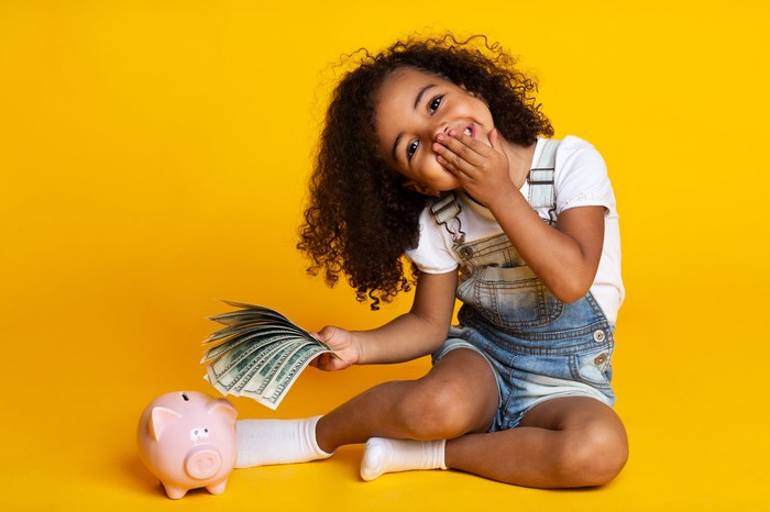 Little girl with a sheaf of money and a piggy bank.