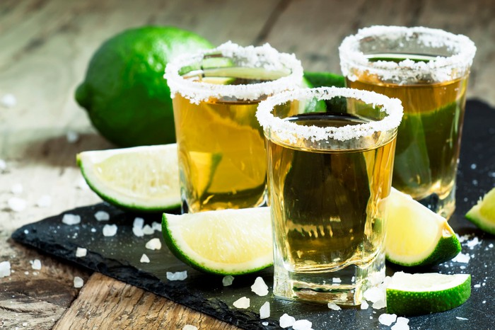 Shot glasses of tequila with lime slices.