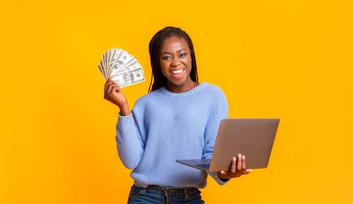 Woman holding laptop and dollar bills.