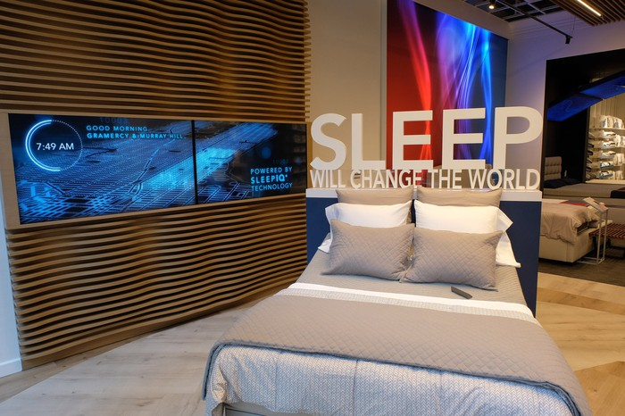 Sleep Number retail store display with bed and Sleep Will Change The World sign