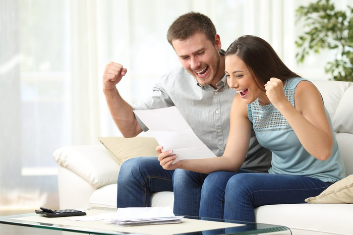 Man and woman sitting on a couch and looking at a piece of paper while they fist-pump excitedly