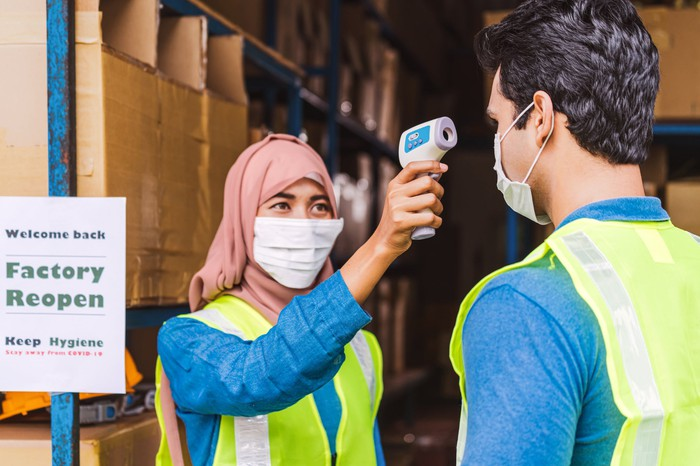 A warehouse employee conducting a temperature check on another warehouse employee.