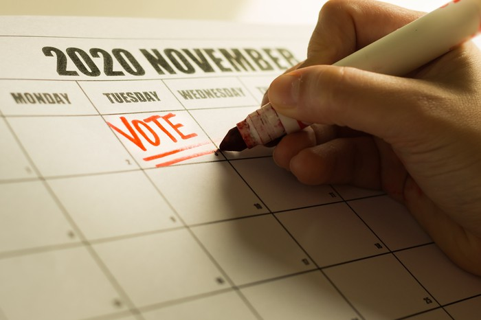 A hand writing the word VOTE on Tuesday the 3rd on a calendar showing November 2020
