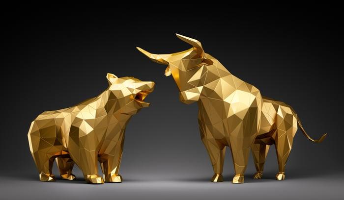 A model of a bear facing a model of a bull.