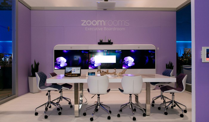 A Zoom Room with a white conference table and chairs
