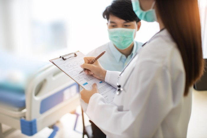 Physician wearing a face mask holding a clipboard and standing next to a patient wearing a mask