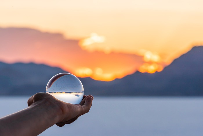 Someone holding out a crystal ball, looking out over a blurred horizon.