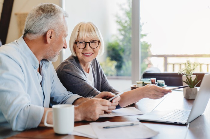 Older man and woman at table with laptop and documents in front of them