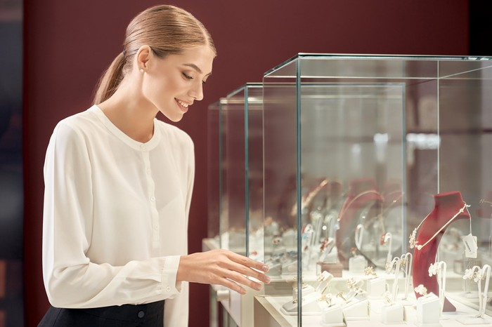 A young woman indicating luxury jewelry inside a glass showcase.