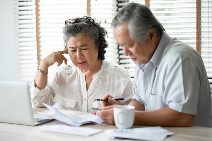 Retirement age man and woman with gray hair looking at financial statements and laptop with concerned expressions.