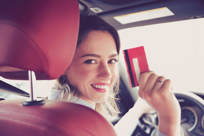 A woman in a driver seat happily flashing a payment card.
