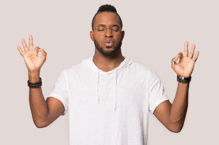 A man makes a meditation gesture while closing his eyes and exhaling.