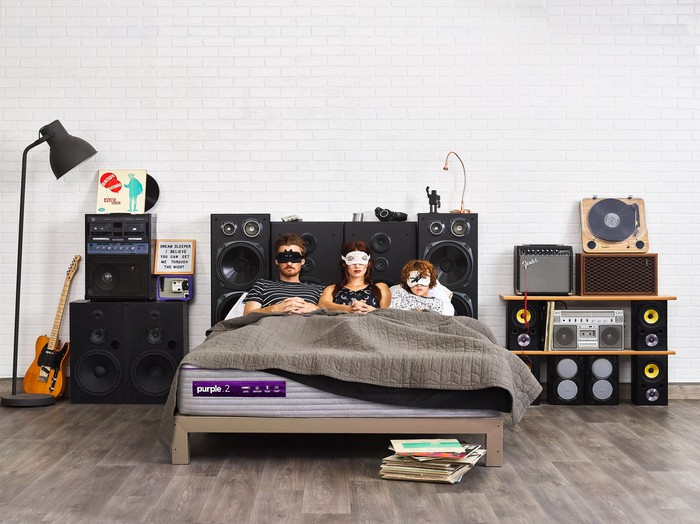 Three people wearing masks lay on a mattress from Purple Innovation in a bedroom setting.