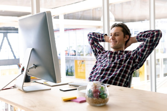 Man with hands behind his head smiling and looking at his computer monitor.