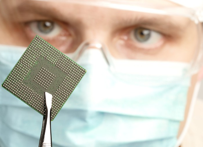 A technician with mask and goggles holds up a microchip with tweezers for a close inspection.