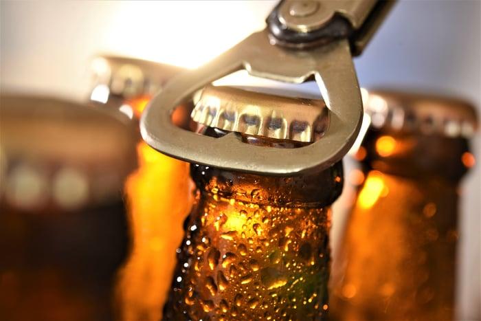 Bottles of beer being opened.