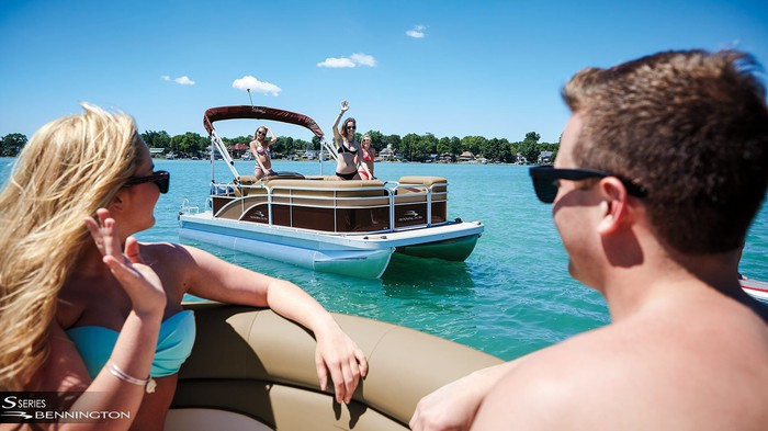 Couples on pontoon boats waving to each other