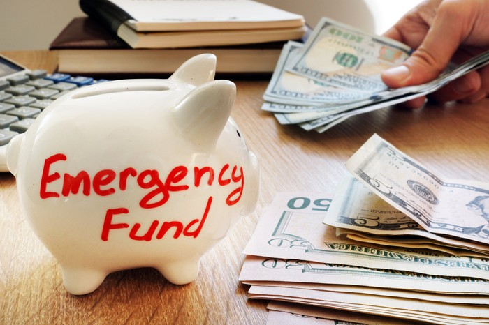 Emergency fund written on piggy bank with cash.