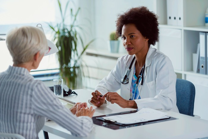 Senior woman sitting across the table from her physician.