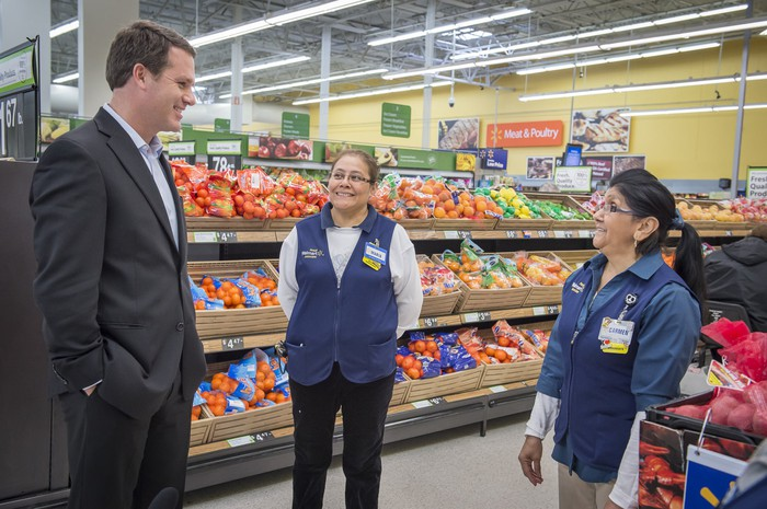 CEO Doug McMillon talking with two associates in a Walmart store produce aisle.