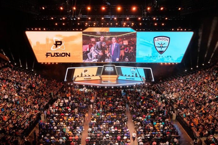 A crowd watching an esports event in an arena.