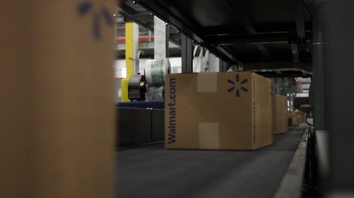 A Walmart.com box on a conveyer belt.