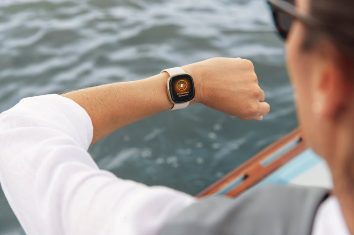 Person on a boat looking at Fitbit sense on their wrist