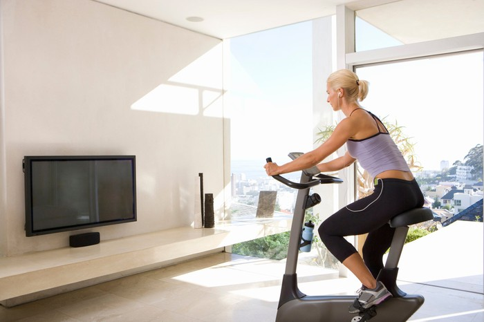woman on home exercise bike in front of flat screen tv