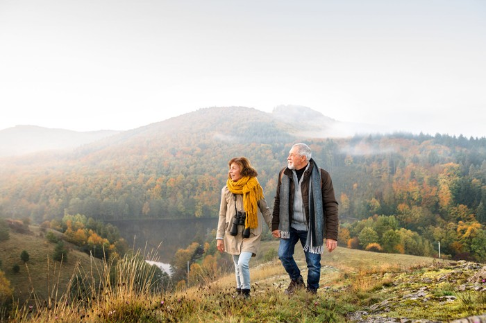 Older man and woman outdoors with mountain in the background