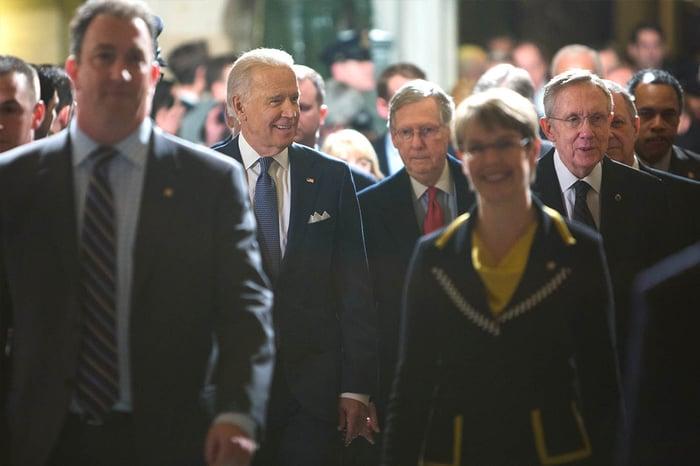 Joe Biden walks with other legislators down a hall.