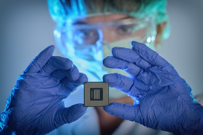 A foundry technician in clean room gear and gloves holds up a completed semiconductor chip.