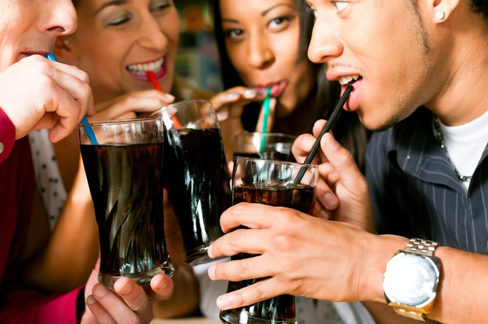 Four young people drinking cola together.