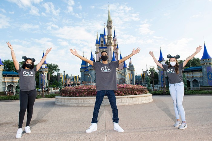 Three young employees wearing masks at Disney World, with the famous castle in the background.
