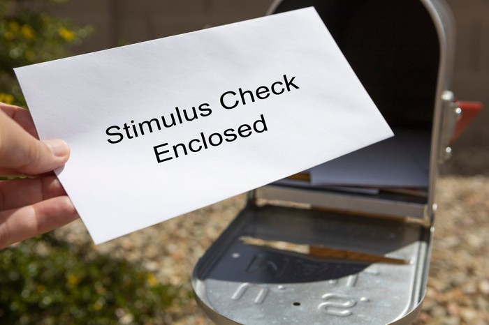 """Hand pulling a white envelope out of a mailbox, with the words """"stimulus check enclosed"""" written on the envelope."""
