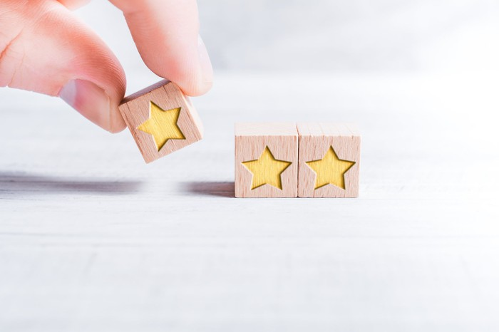 Fingers putting a wood block with a star next to two identical wood blocks with stars
