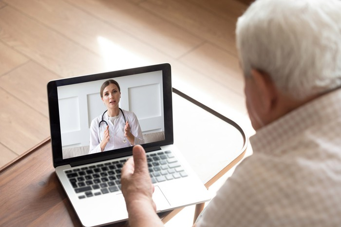 An older person looking a physician on a laptop screen