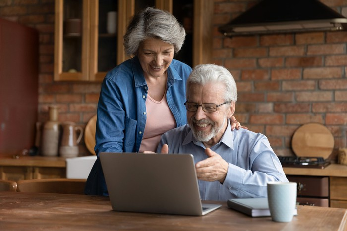 Smiling older couple looking at laptop