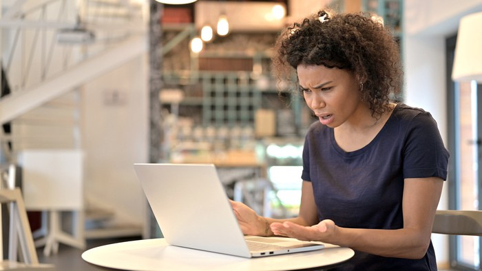 Distraught young woman looking at her laptop