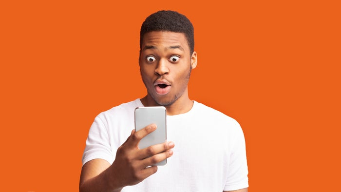 A young person looks at a cellphone with a shocked expression.