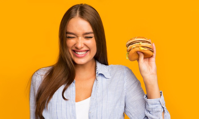 A young woman holds a burger.