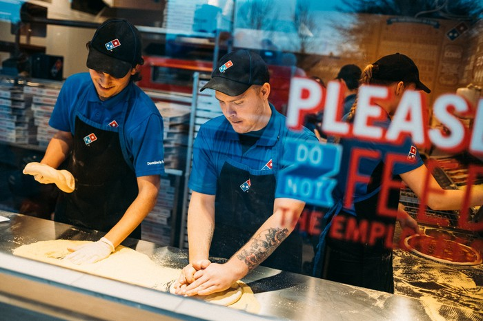 Two Domino's employees make a pizza.