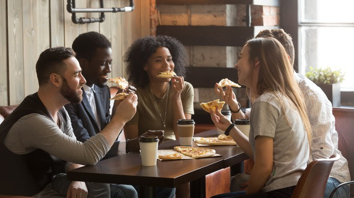 A group of friends eat pizza and drink coffee.