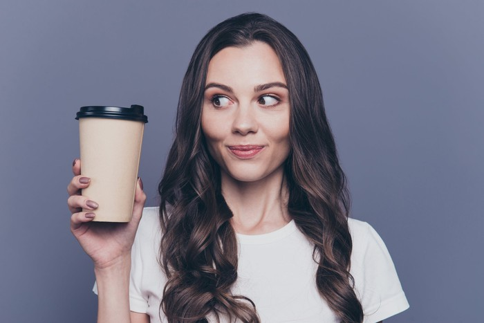 A woman holding a to-go coffee cup