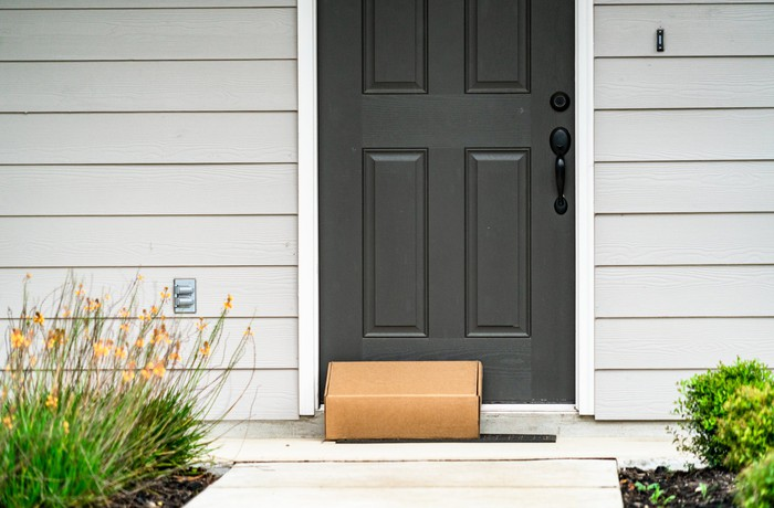 A package sits by a front door.