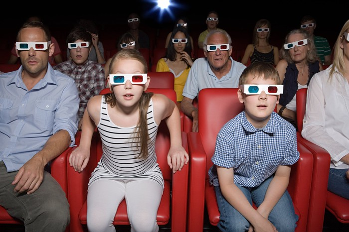An audience wearing 3-D glasses staring forward, with a projector light visible in background.