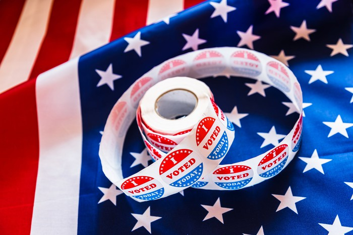 """An American flag with a roll of """"I Voted"""" stickers on it"""